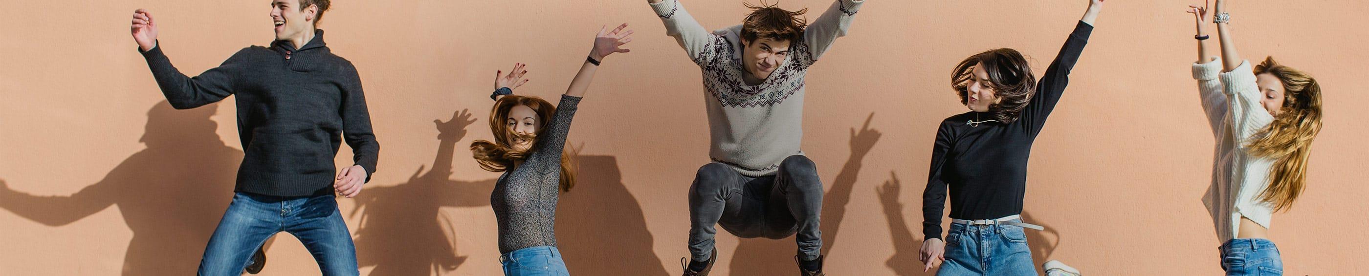 Tökéletes időzítésű kép egy baráti csoportról, akik felemelt karokkal a levegőbe ugranak