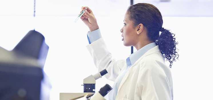 Orvosi köpenyt viselő nő kémcsövet ellenőriz