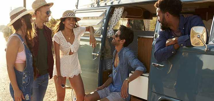 Egy baráti társaság kisbuszuk mellett beszélget a napsütésben