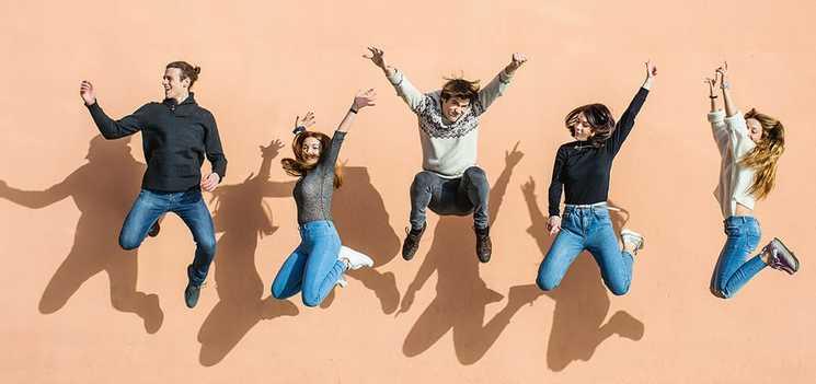 Egy baráti csoport tagjai a levegőbe ugranak, nevetnek és mosolyognak