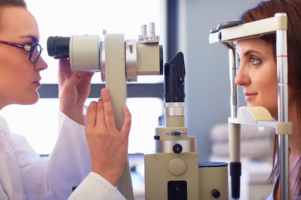Egy szemészeti szakember és egy fiatal nő retinakamerán néz át, oldalnézetből