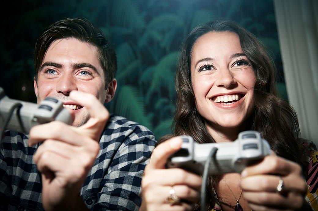 Két felnőtt játékvezérlőt tart a kezében és videójátékot játszik