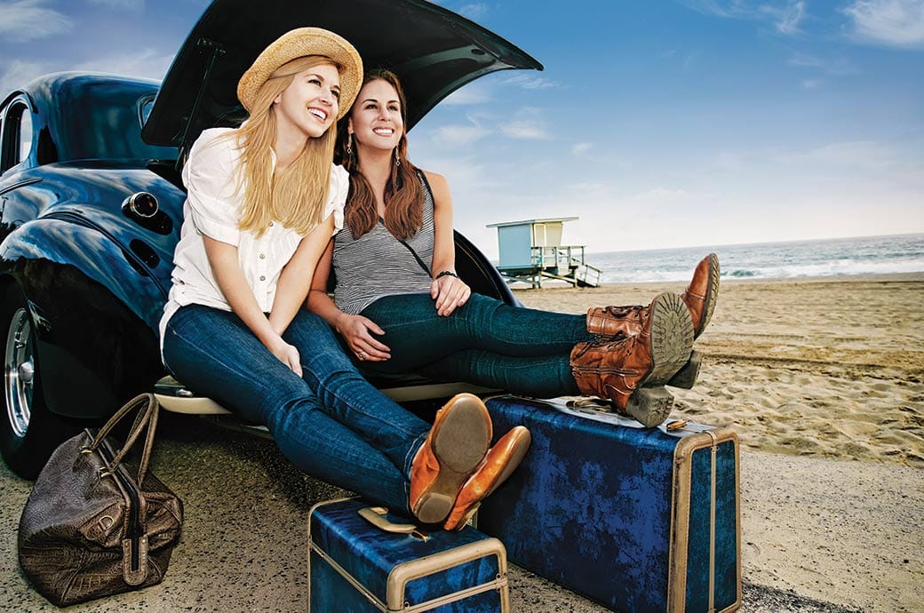Két lány egy autó csomagtartójában ül a strandon csomagjaikkal, készen a nyaralásra.