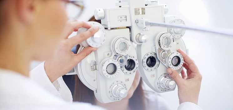 Egy szemészeti szakember képe, aki éppen egy látásvizsgáló készüléket állít be